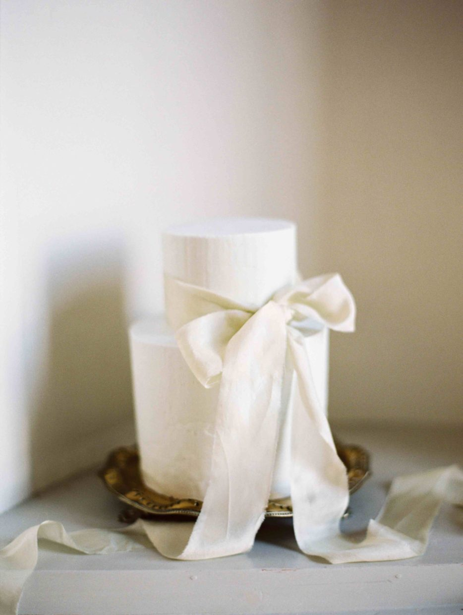 Understated elegant buttercream wedding cake tied with a silk ribbon. Featured on Style Me Pretty