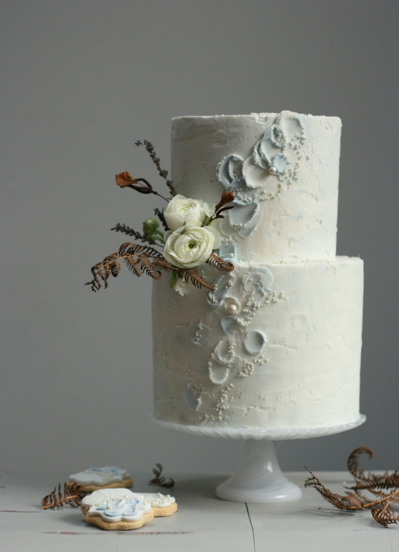 Watercolour buttercream wedding cake in shades of blue, grey and ivory. Decorated with dried flowers and ranunculus