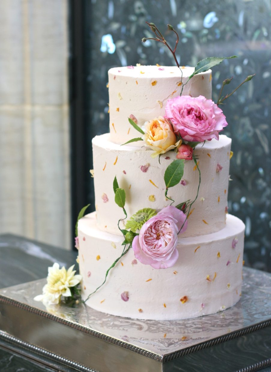 Delicate pink buttercream wedding cake decorated with edible flower petals and garden roses at Gravetye Manor