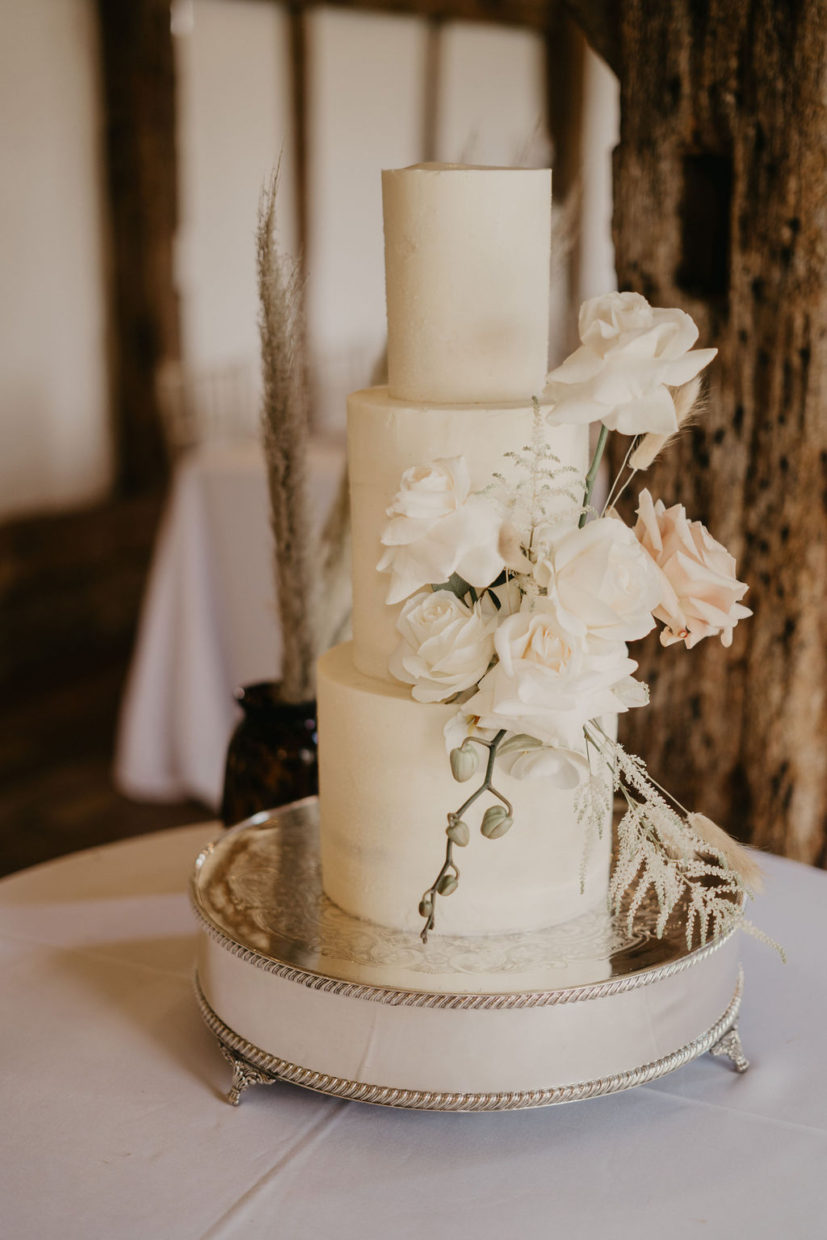 White buttercream wedding cake decorated with blush and ivory flowers | Sugar Plum Bakes | Sophie Jane Photography