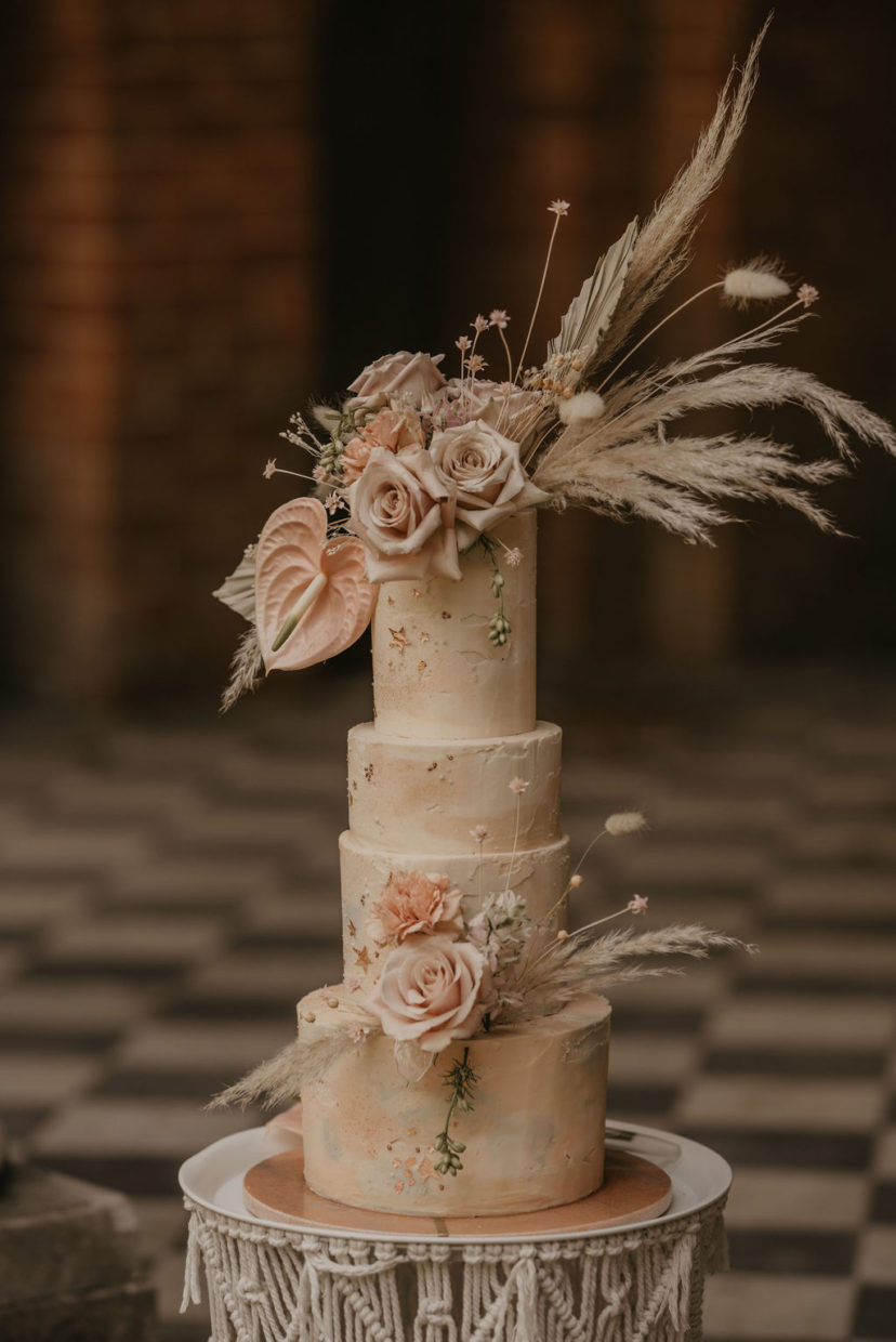 Boho buttercream wedding cake in nude, blush and sage green colours. Decorated with fresh and dried flowers and touches of rose gold