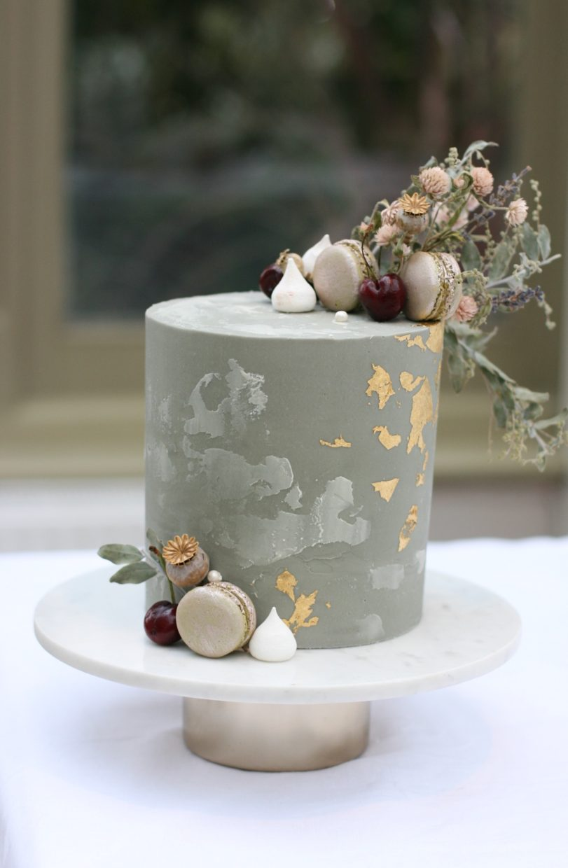 Modern buttercream wedding cake in urban concrete finish with flecks of gold and dried flowers at Hampton Court House