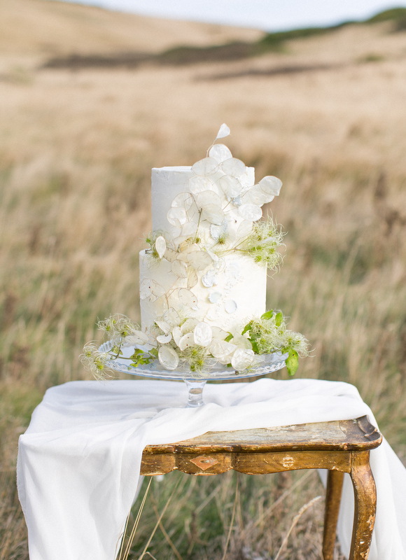 Elegant buttercream wedding cake decorated with foliage
