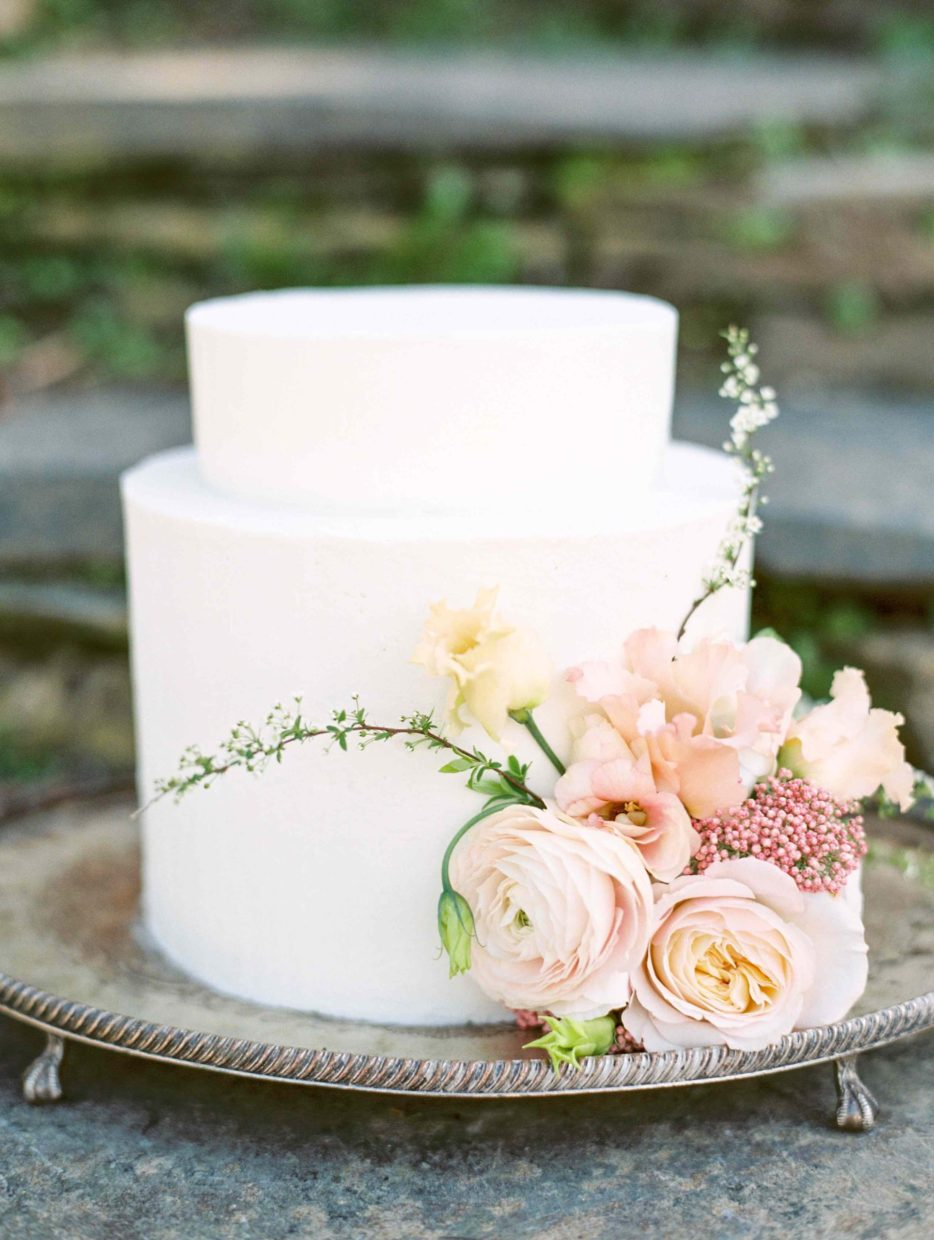 Understated and elegant buttercream wedding cake decorated with blush pink flowers