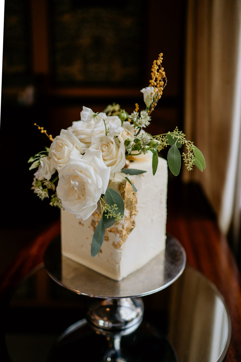 Modern square buttercream single tier wedding cake decorated with fresh flowers and edible gold leaf | Elena Popa