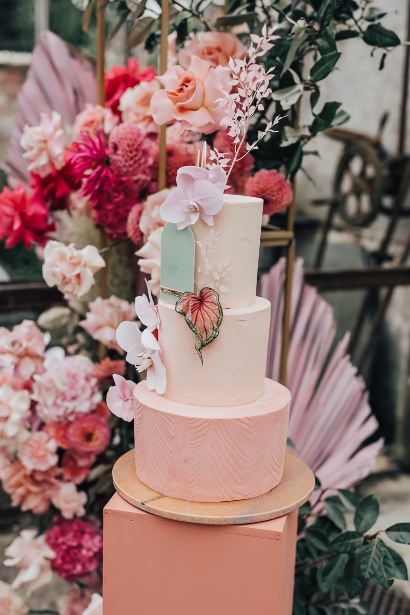 Pink tiered buttercream wedding cake decorated with fresh orchids and modern sugar details